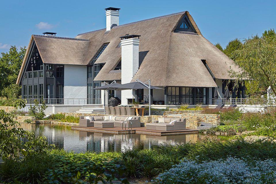 Prachtige moderne witte villa met rieten dak veel raampartijen en