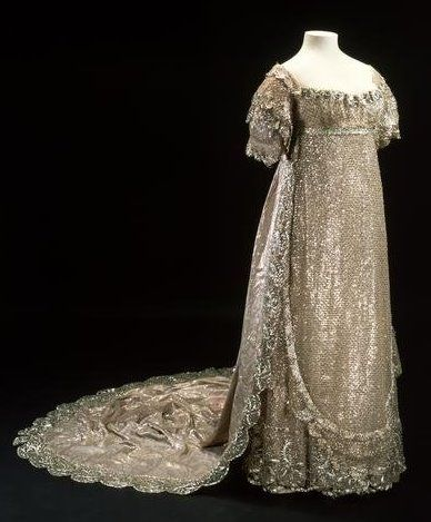 """Cloth-of-silver"" (silk bobbinet embroidered with heavy silver lamé) wedding dress with white silk satin lining and silver metallic-thread embroidery, English, c. 1816. Made by ""Mrs. Triaud of Bolton Street"", and worn by Princess Charlotte for her wedding to Prince Leopold. The dress required ""500 hours of detailed hand-stitching in ultra-fine, mono-filament silk threads, almost invisible to the naked eye."""