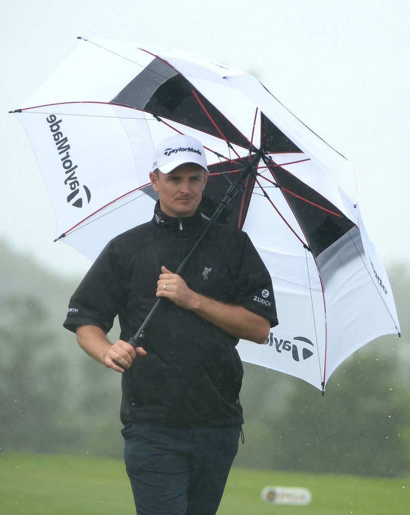 Justin Rose of England takes cover from the rain during the final round of the PGA Grand Slam of Golf at Port Royal Golf Course on October 16, 2013 in Southampton, Bermuda.