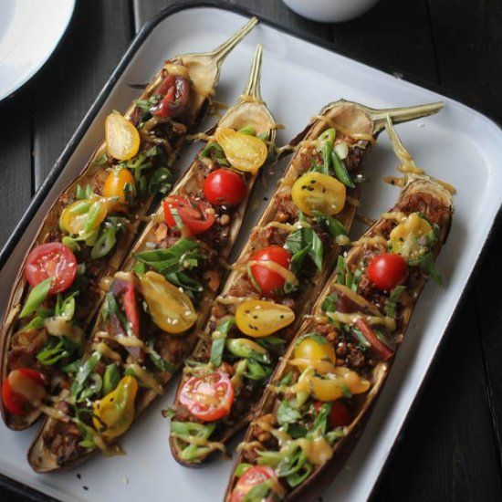 Stuffed Miso Eggplant, topped with fresh cherry tomatoes, basil, and a sweet miso dressing.