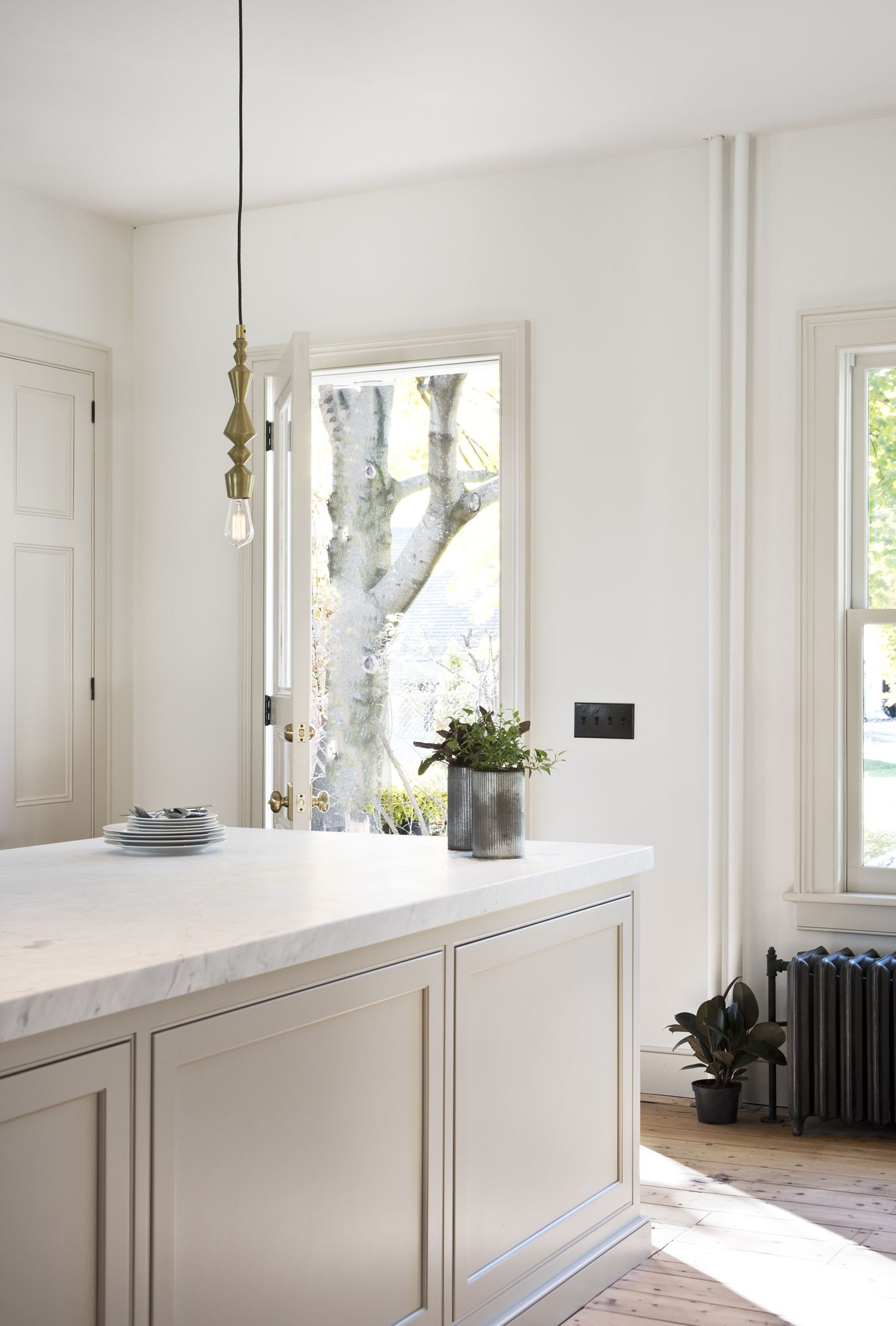 honed Carrara counters and off-white cabinetry create a soft, bright look for a modern kitchen in a historic renovation, bronze colored switches add to the historic feel