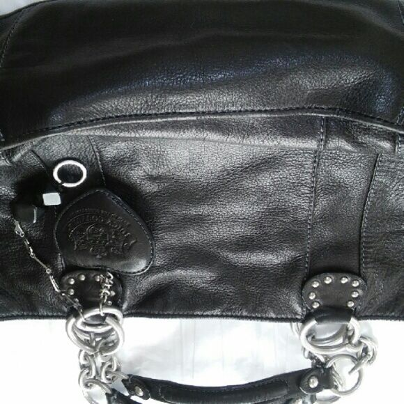 Juicy Couture black leather handbag Outside of purse is in very good condition, inside has some ink stains.  Has brushed silver toned hardware, 2 inside wall pockets, one w/zipper, 1pocket for lipstick.  Has Couture bag charms. Pre-owned, make it yours! Bags Satchels