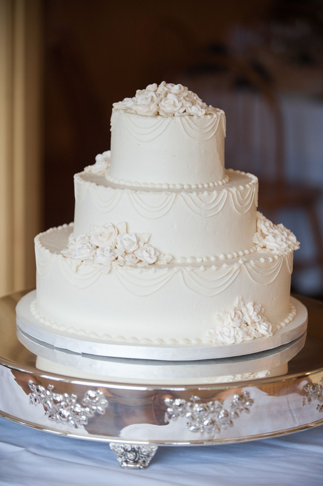 Beautiful classic white wedding cake, three tier on a silver platter ...