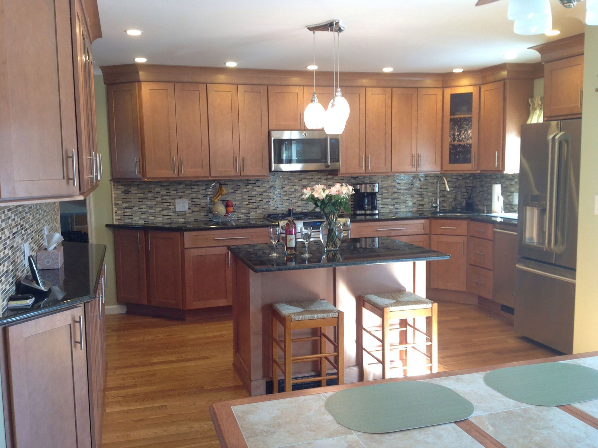 large kitchen has semi custom maple cabinets in a Shaker ... on Maple Kitchen Cabinets With Black Countertops  id=37438