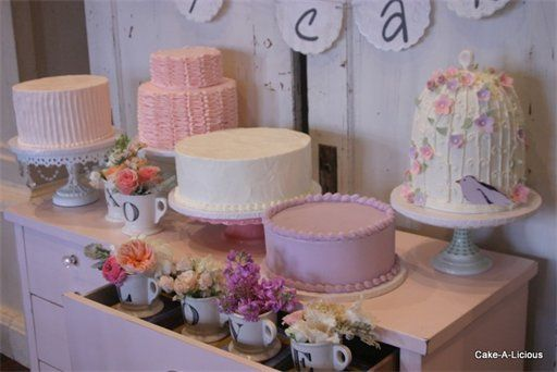 i like the multiple pretty cakes & the love cups & doilies on the wall!