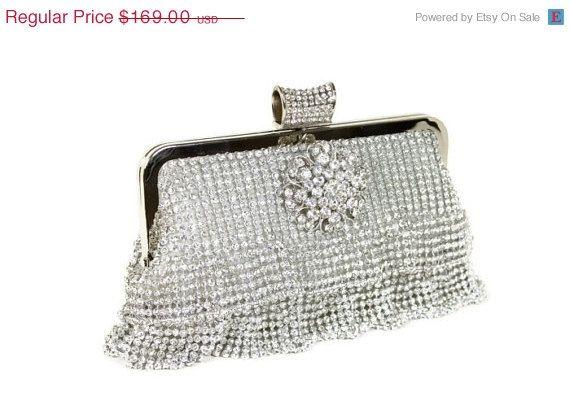 Stunning rhinestone ruffle clutch with crystal brooch and rhinestone studded closure.