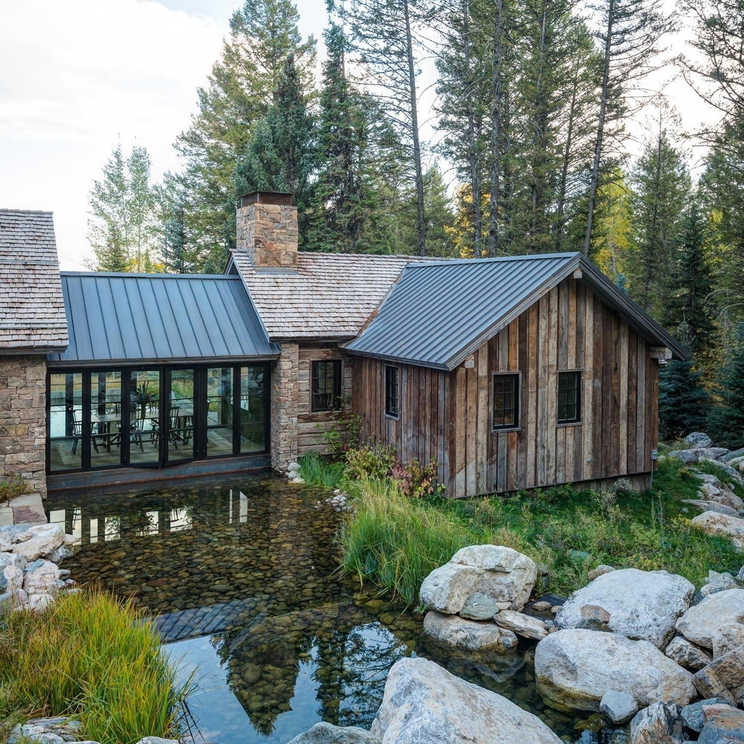 Beautiful Wood And Stone Building With Grassy Area And River Looks Like There S A Table Area In The Glass Corridor Ov House Exterior Architecture House Design