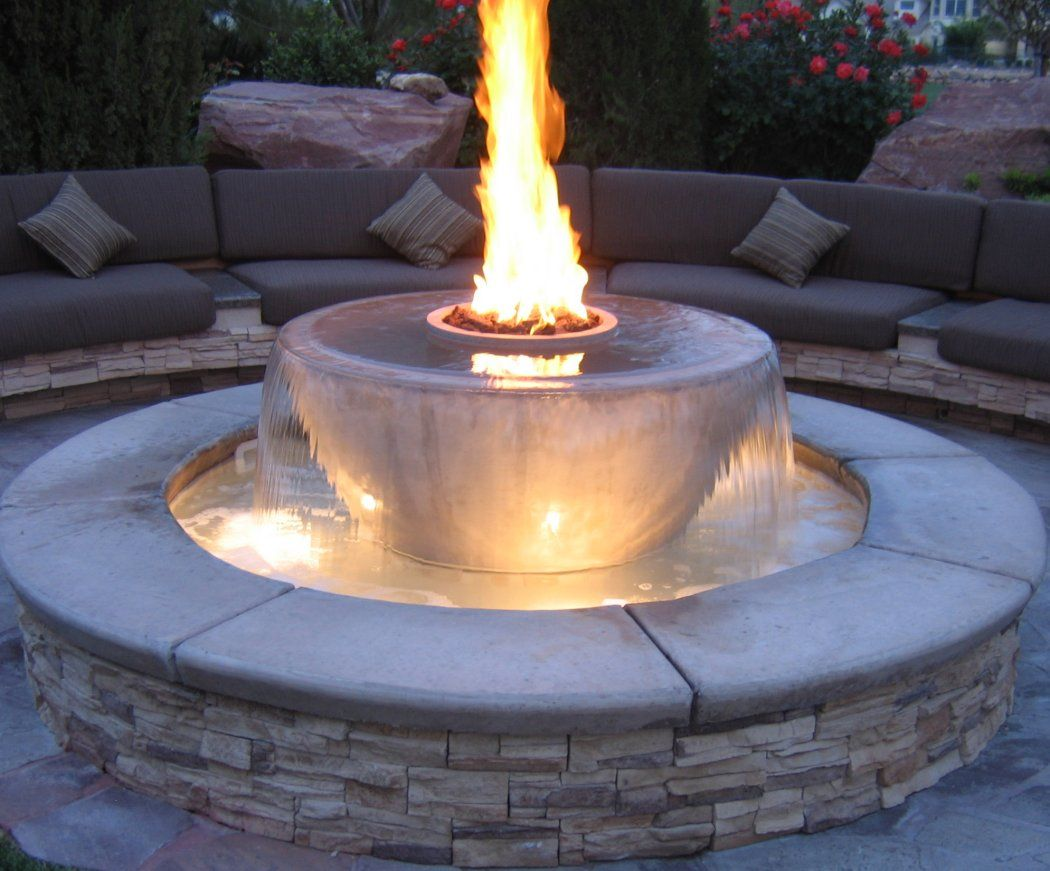Custom outdoor living area with stone benches and fire bowl