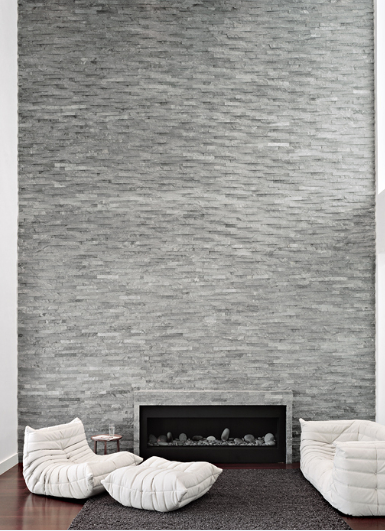 dramatic fireplace wall with single material extending floor to ceiling