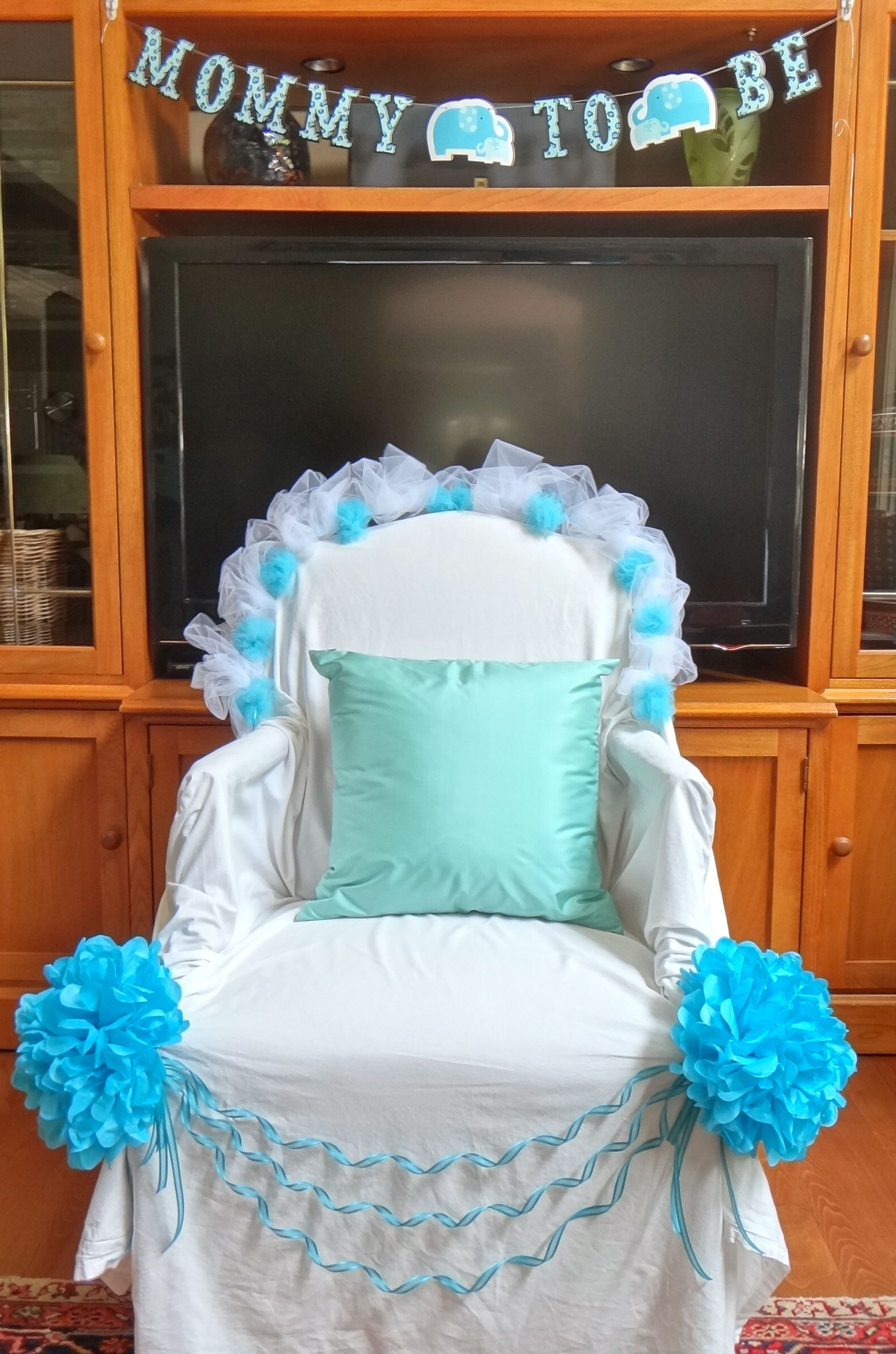 Mom to be thrown Chair draped with a white bed sheet and decor