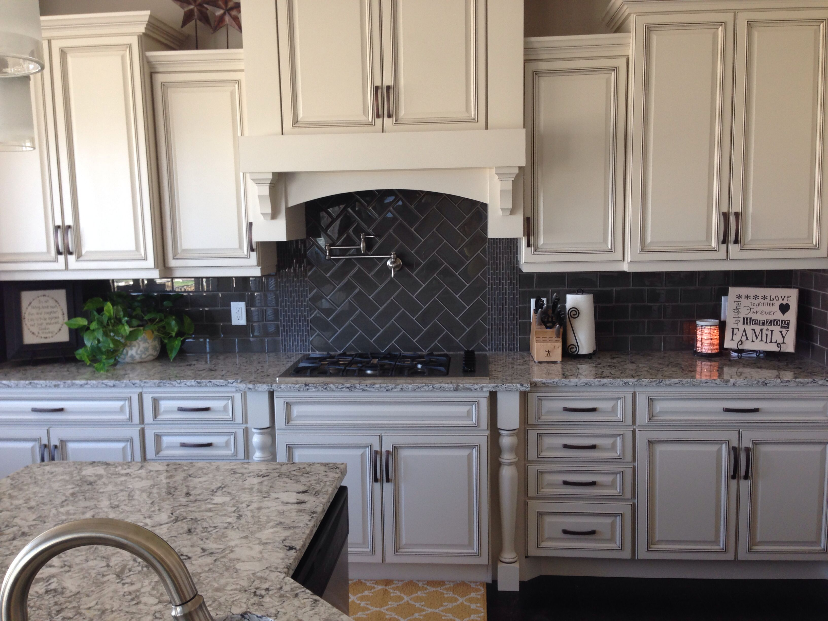 Glass subway tile backsplash with herringbone pattern