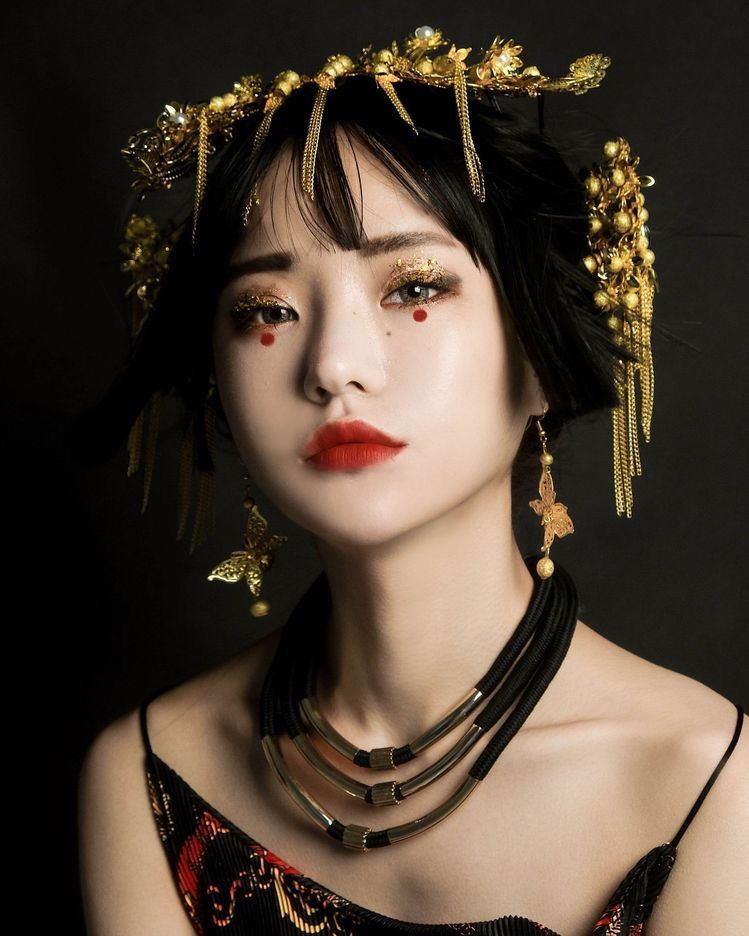 Photo of Asian women, neutral face, red lips, golden shimmering eyeshadow, red …