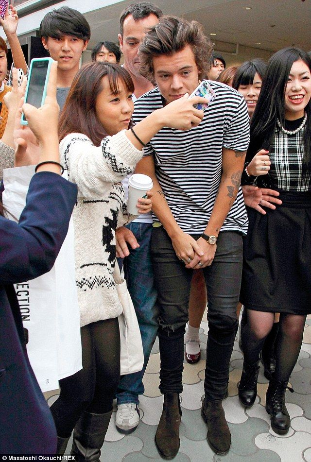 Harry Styles is mobbed by excited fans upon arrival in Tokyo