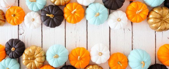 Fall double border banner of colorful pumpkins Above view over a white wood background with copy space