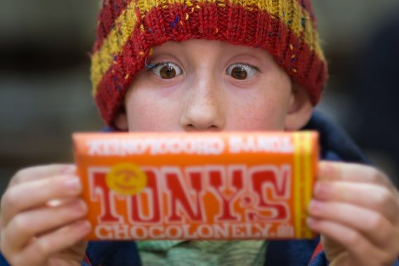 9d712291202 A little boy wearing a striped beanie reading the label of a chocolate bar  in Portland