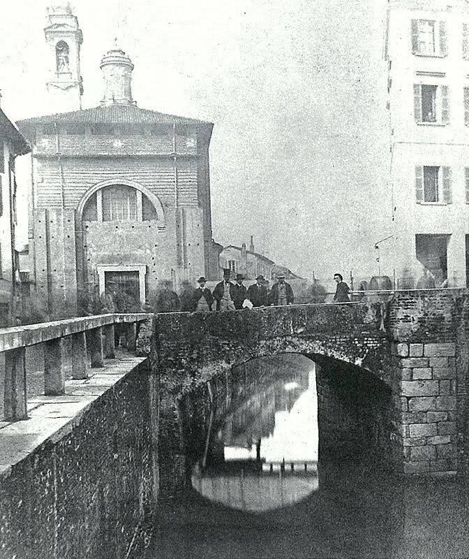 Porta Ticinese, il vecchio ponte che scavalcava la cerchia dei navigli all'altezza della porta, oggi tra via De Amicis e via Molino delle armi. Sullo sfondo, la chiesa di santa Maria della Vittoria. Nel 1880 il ponte fu sostituito con un nuovo manufatto, la foto è pertanto antecedente di qualche anno.