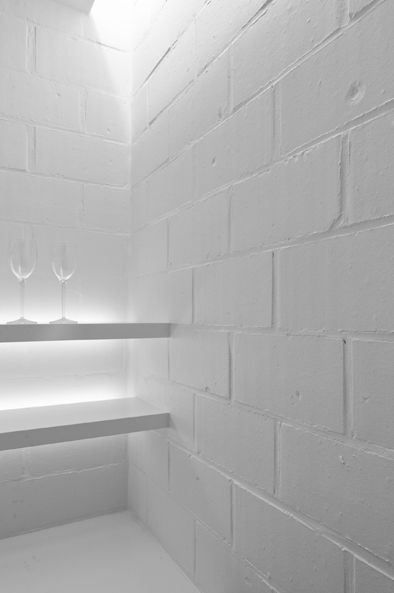 Backlit shelves and white painted brickwork inside an interior by ...
