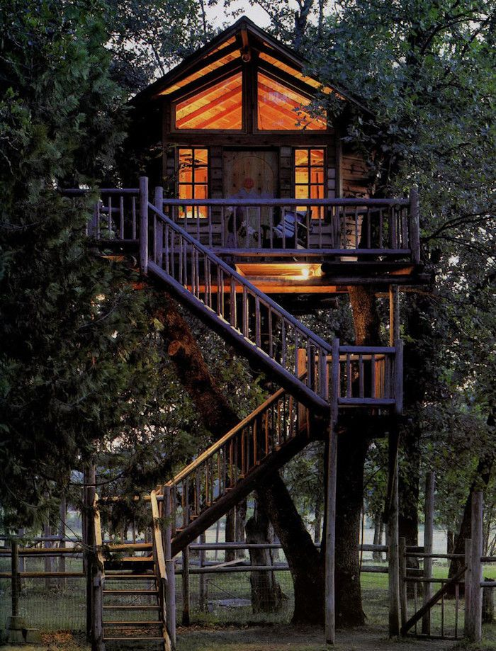 High above the ground  tree house with several windows illuminated from lamps inside accessible through three sets of stairs also ideas for cozy and incredibly cool houses rh pinterest