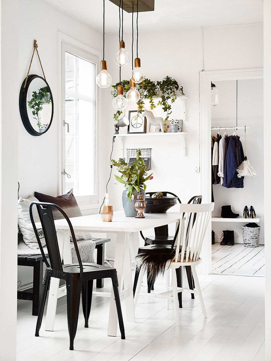 Black chairs and a group of pendants lights give this nordic kitchen