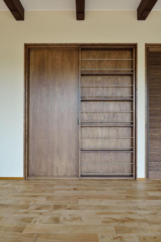 リビングの引き違い戸はガレージと階段につながります。建具には本棚を造り付けしました。