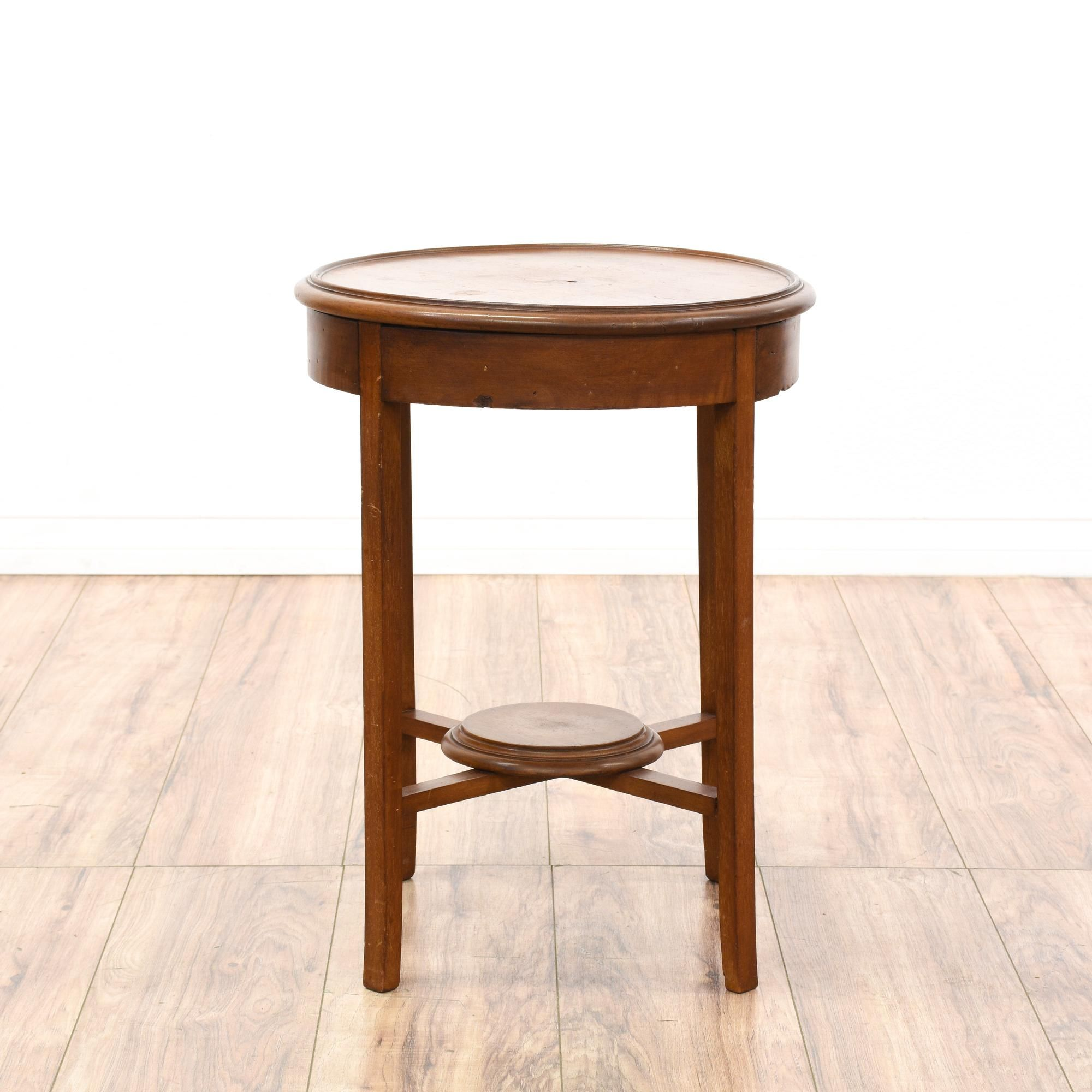 This small round side table is featured in a solid wood