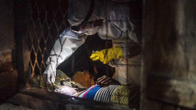 Ebola疫区里的五个片段:谁能活下来,谁要死去?塞拉利昂,世卫组织的何塞·罗维拉(Jose Rovira)医生从一位疑似埃博拉死者身上棉签取血。图片来源:Tommy Trenchard  埋葬遗体 丹尼尔•詹姆斯(Daniel James),红十字会志愿者  凯拉洪,塞拉利昂  在一个叫做葛白尼瓦路(Gbanyawalu)的村庄,我们埋葬了第一具尸体。当把尸体翻过来擦洗的时候,它吸了口气—�