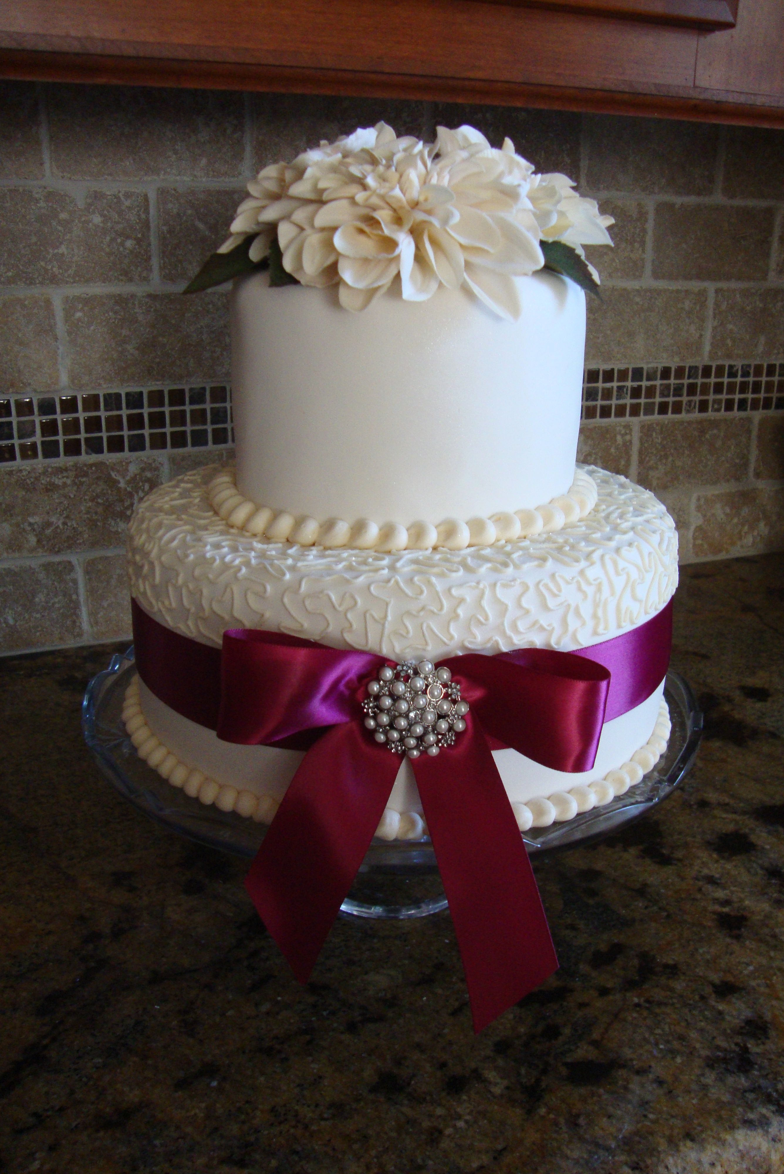 Two tier wedding cake decorated with merlot ribbon and