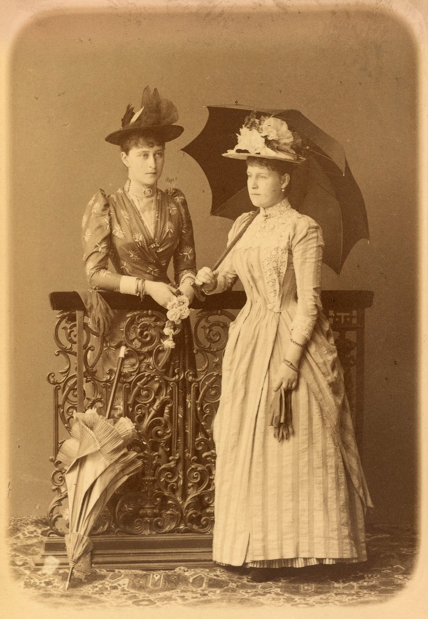 Grã-duquesa Elisabeth Feodorovna (1864-1918) e Grã-duquesa Alexandra Georgievna (1870-1891) em cerca de 1890. A grã-duquesa Elisabeth está de pé atrás de uma cerca de ferro forjado, vestindo um vestido modelado e segurando um pequeno ramo de flores. Há um guarda-chuva fechado encostado na cerca na frente dela. Grã-duquesa Alexandra está de pé na frente da cerca para a direita, segurando um guarda-chuva atrás dela com a mão direita e segurando um par de luvas na mão esquerda.