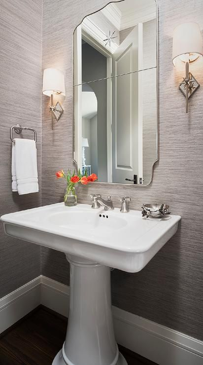 Gray powder room features walls clad in gray sisal wallpaper lined with a curved chrome mirror ...