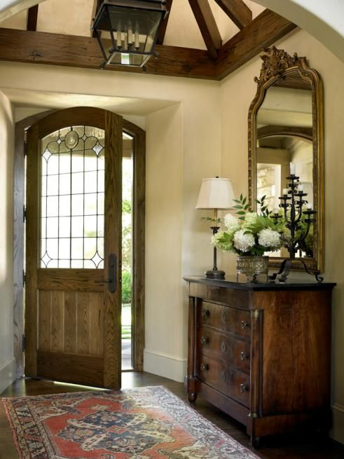 Very english feel to this foyer....love the chest, mirror, rug ...