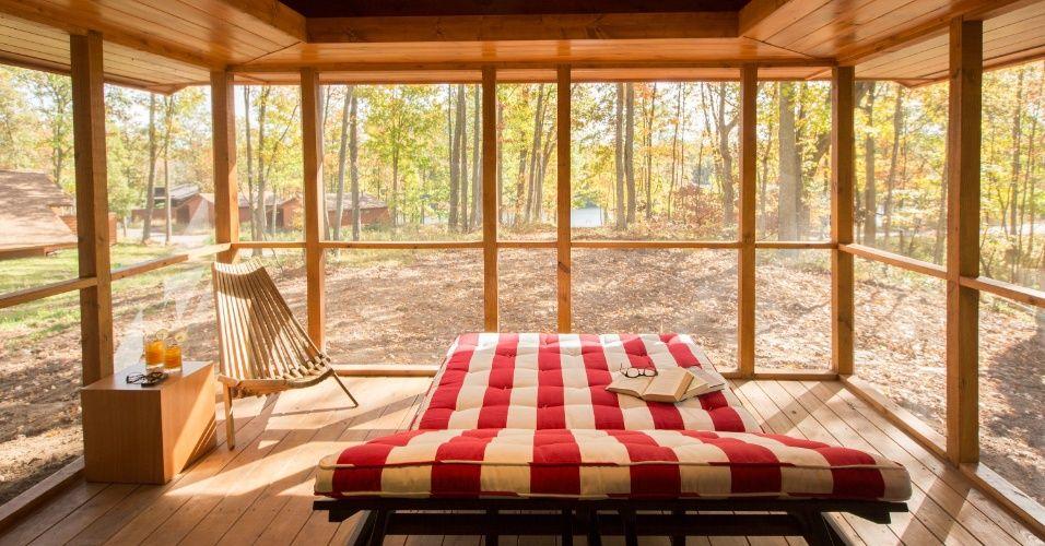 """Com vista para o lago, a varanda é o principal cômodo da casa de campo """"Escape"""". No ambiente, que conta com uma espreguiçadeira, é possível relaxar e apreciar a paisagem. A versão original da construção móvel fica situada no resort Canoe Bay, próximo à cidade de Chetek, no estado de Wisconsin (EUA)"""
