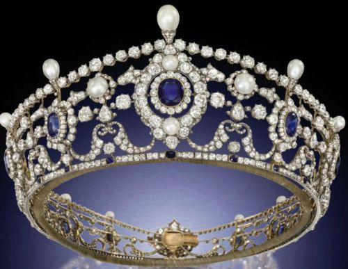 The Portland Antique Sapphire,Diamond and Natural Pearl Tiara.        Designed as a series of twelve graduated cushion-shaped sapphire and old-cut diamond clusters to the openwork frame of diamond-set swag and husk motifs, embellished with bouton-shaped pearls and diamond line borders to the pear-shaped pearl finials and sapphire collet accents, mounted in silver and gold, circa 1890.