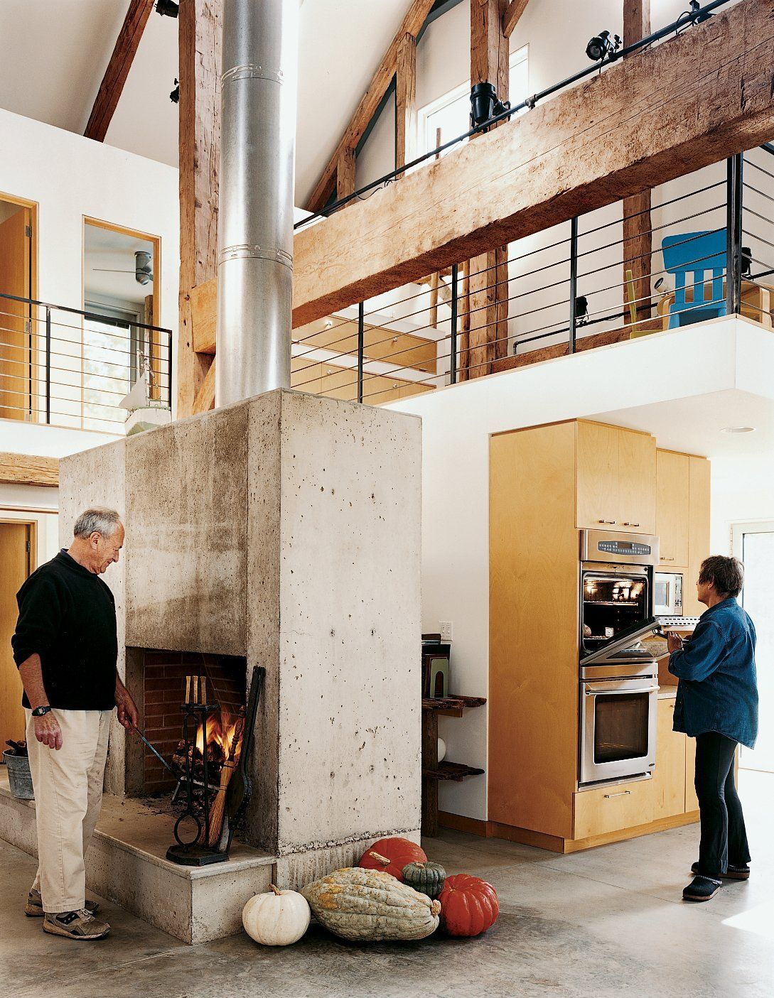 In keeping with the Goodmans' desire for just enough subdivision for rooms to sleep and work in, Cohen inserted a two-story volume into one of the barn frame's side aisles. An additional small mezzanine over the kitchen serves as a play area for the grandchildren. Tagged: Kitchen, Wall Oven, Concrete Floor, Wood Cabinet, and Microwave. Photo 13 of 14 in 13 Brilliant Barn Conversions That Merge Past and Present from Raising the Barn