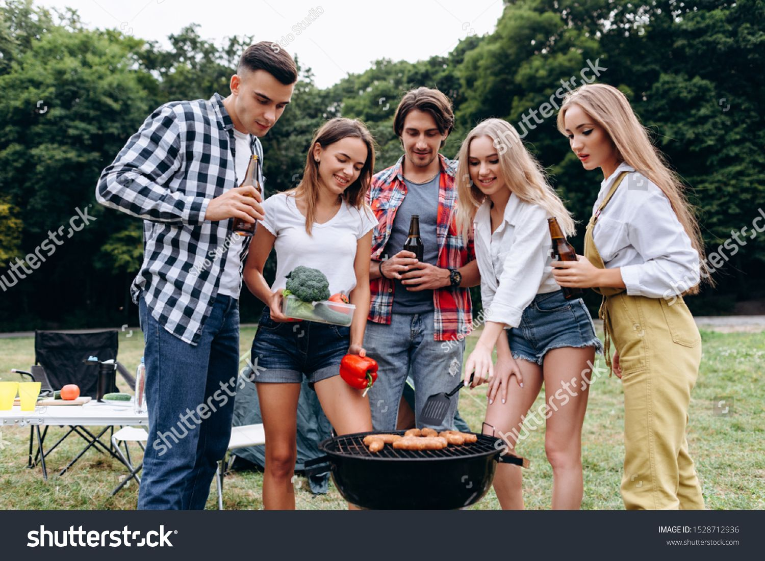 A company of friends with a drinks and food cooking on the barbecue in the camping   Image