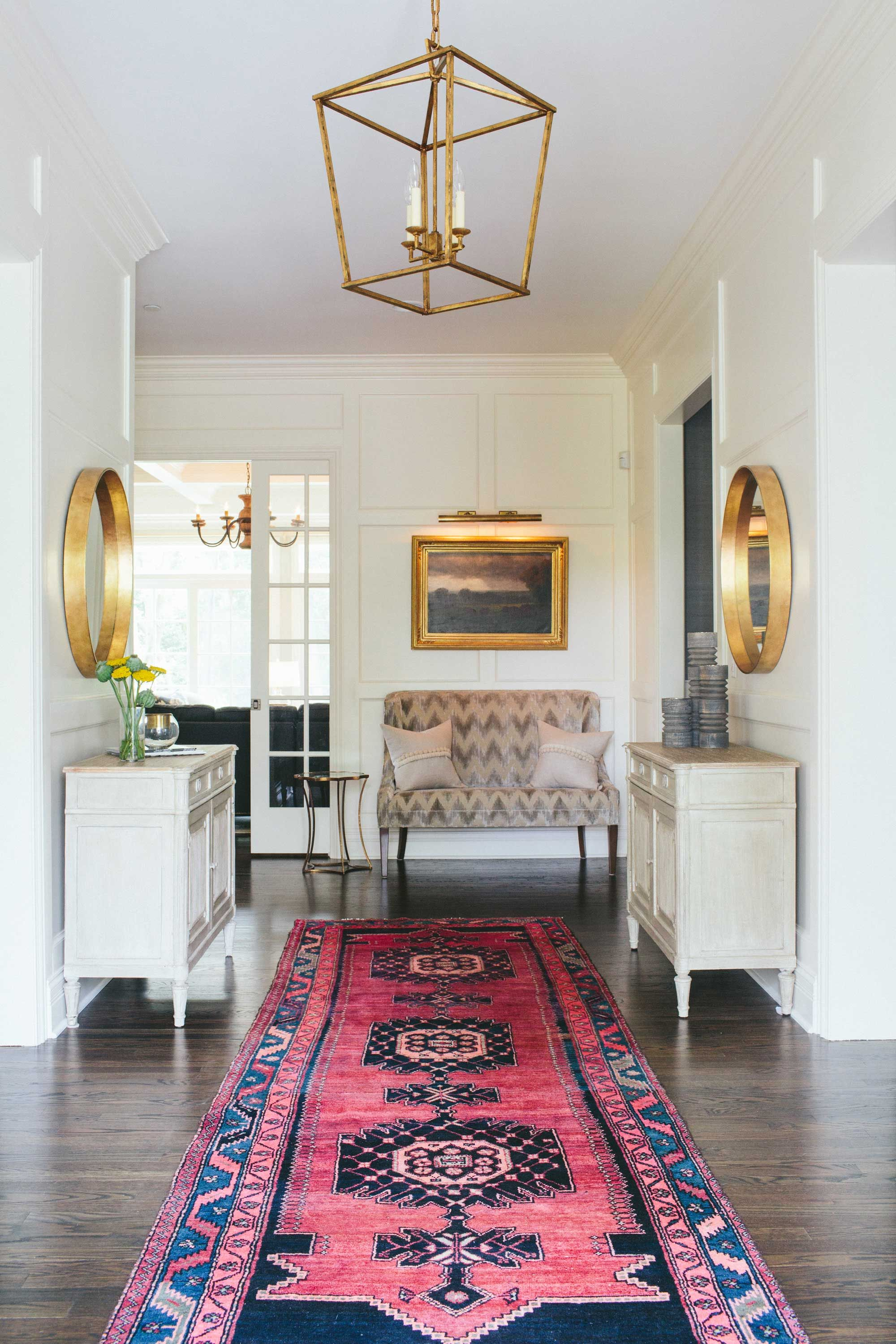 Long colorful rug runner into a neutral and gold foyer