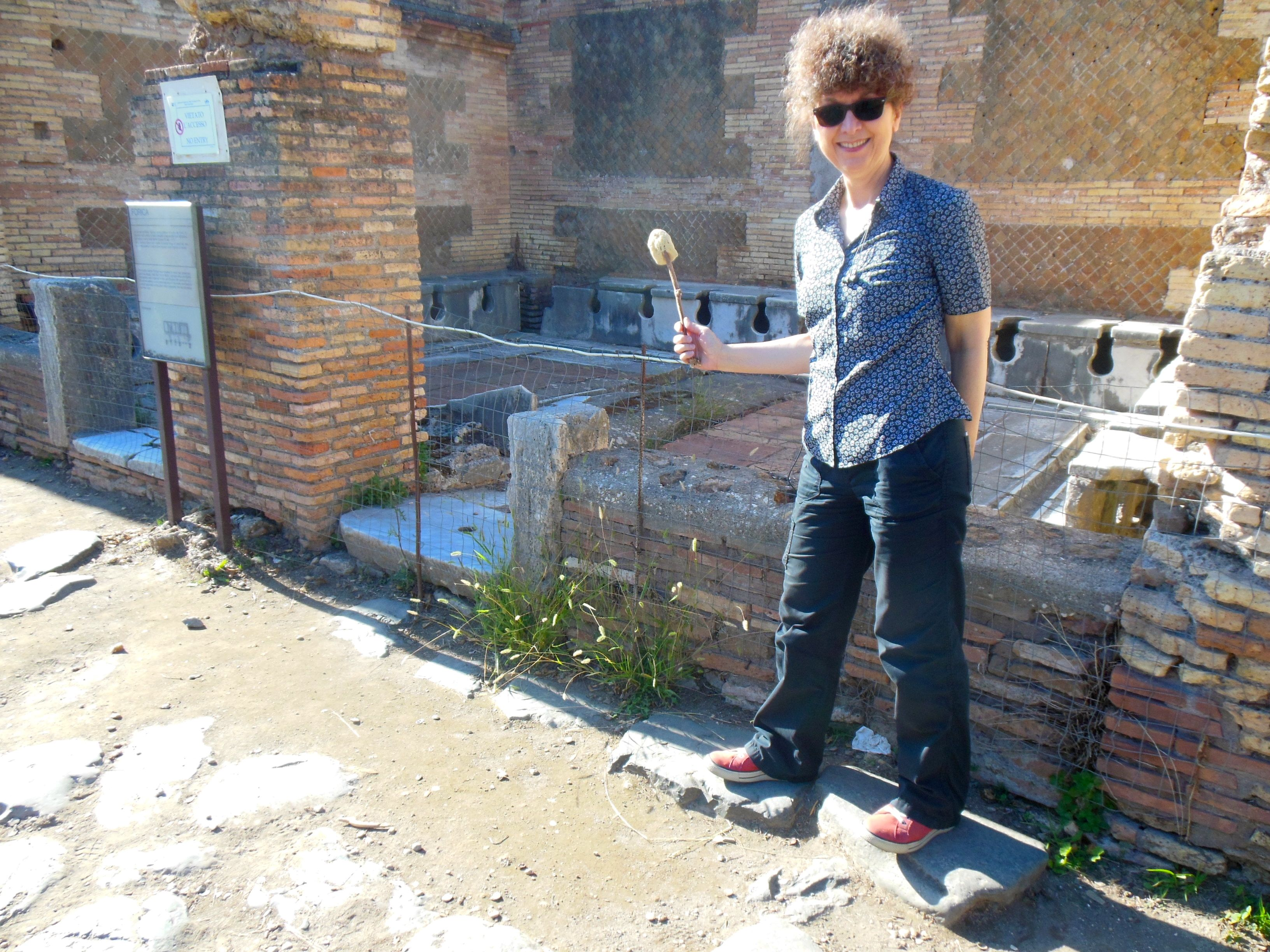 Roman Mysteries author Caroline Lawrence with a sponge-stick by the latrines in Ostia Antica. Sept 2013.