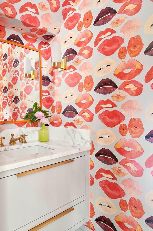 Photo of Clad in Voutsa Lips on Silver Wallpaper, this glamorous powder room boasts a lig…
