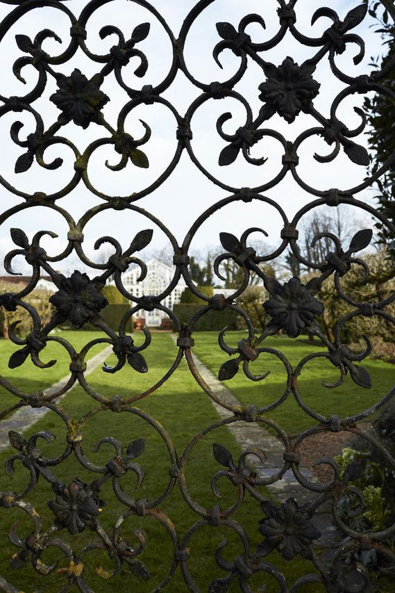 Elaborate iron gates on a pathway leading to the white-painted greenhouses on the grounds of Dunsborough Park, a 1580 English estate.