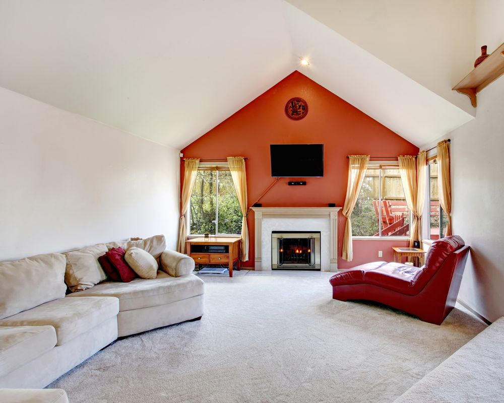 The bold orange accent wall painted in dutch boys court jester b21 1 lengthens the space and draws the eye to cozy fireplace at the heart of the room