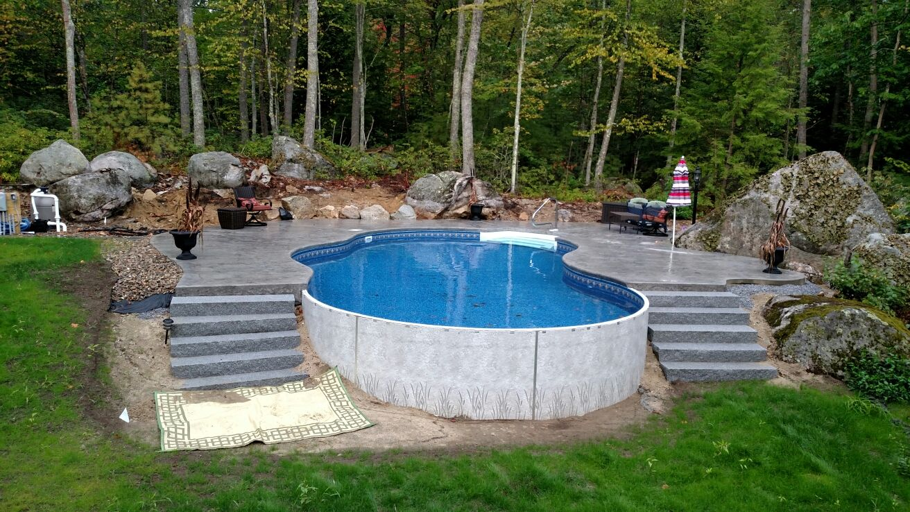 Radiant 18x32 freeform built into a hill with stamped for Above ground pool decks for small yards