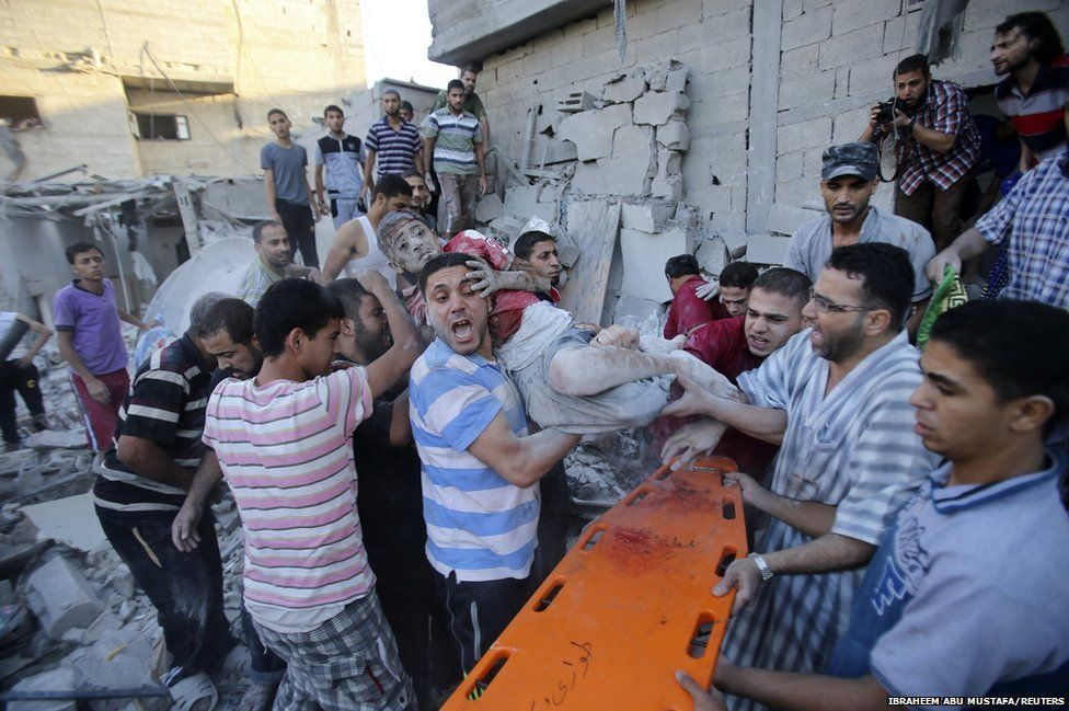 Palestinians carry a wounded boy who was evacuated from under the rubble of a house, which witnesses said was destroyed in an Israeli air strike, in Rafah in the southern Gaza Strip, 3 August 2014