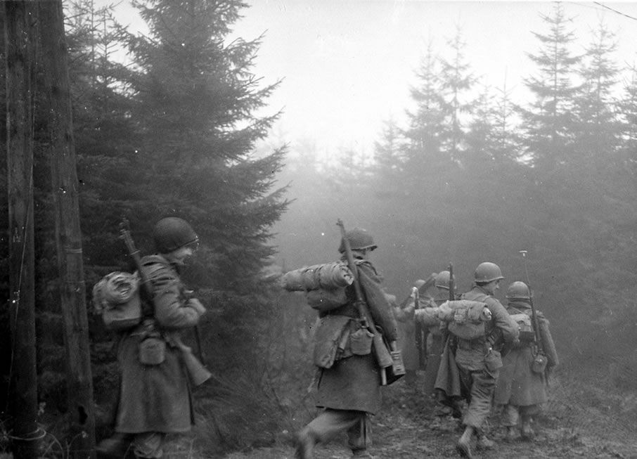 Men of the 82nd Airborne Division move up a road through heavy fog, somewhere near Werbormont, Belgium.