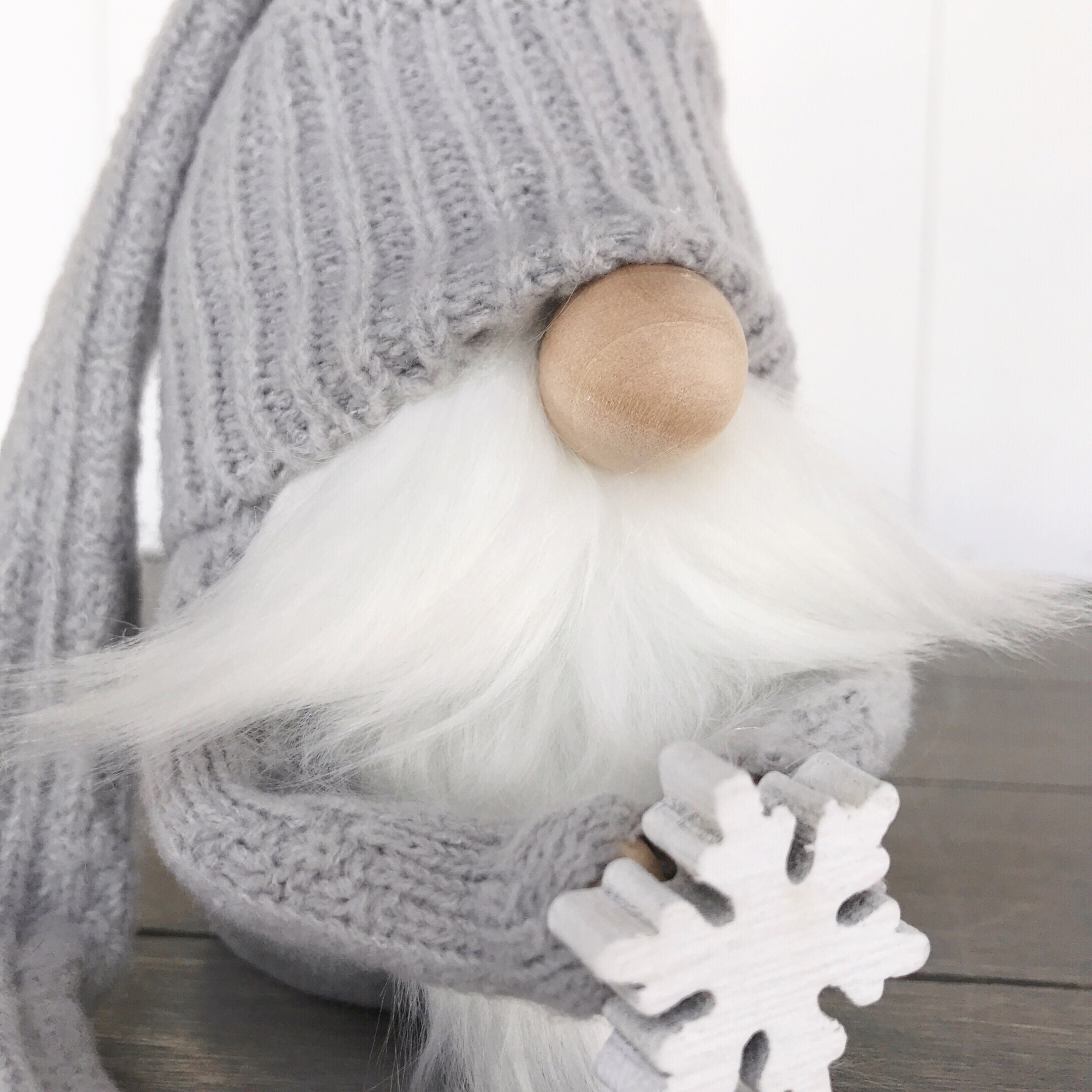 Neutral gray winter gnome holding a snowflake Winter