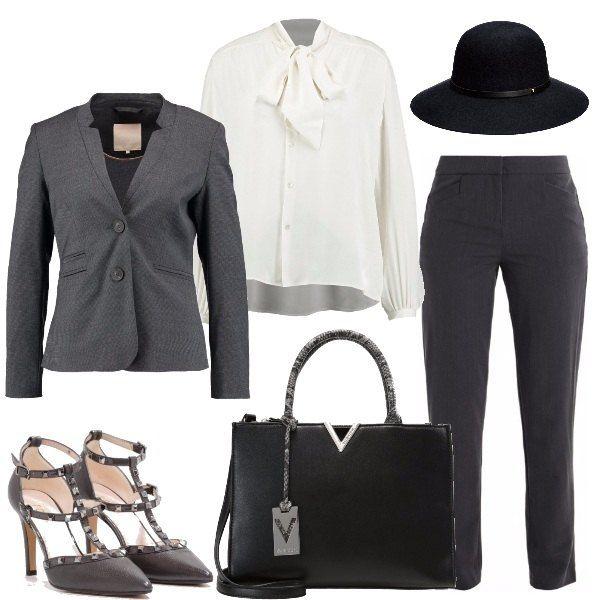 Sicura e decisa col completo grigio, giacca due bottoni, sotto la femminilissima camicia col fiocco, le scarpe a punta con le borchie, grande borsa rigida, completa a dare un tocco unico, il cappello con tesa.