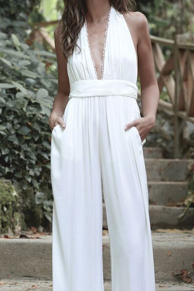 Stunning white halter style jumpsuit with a deep V-neckline and loose wide leg pants. Belted at the waist for a flattering silhouette. Pockets complete the look.