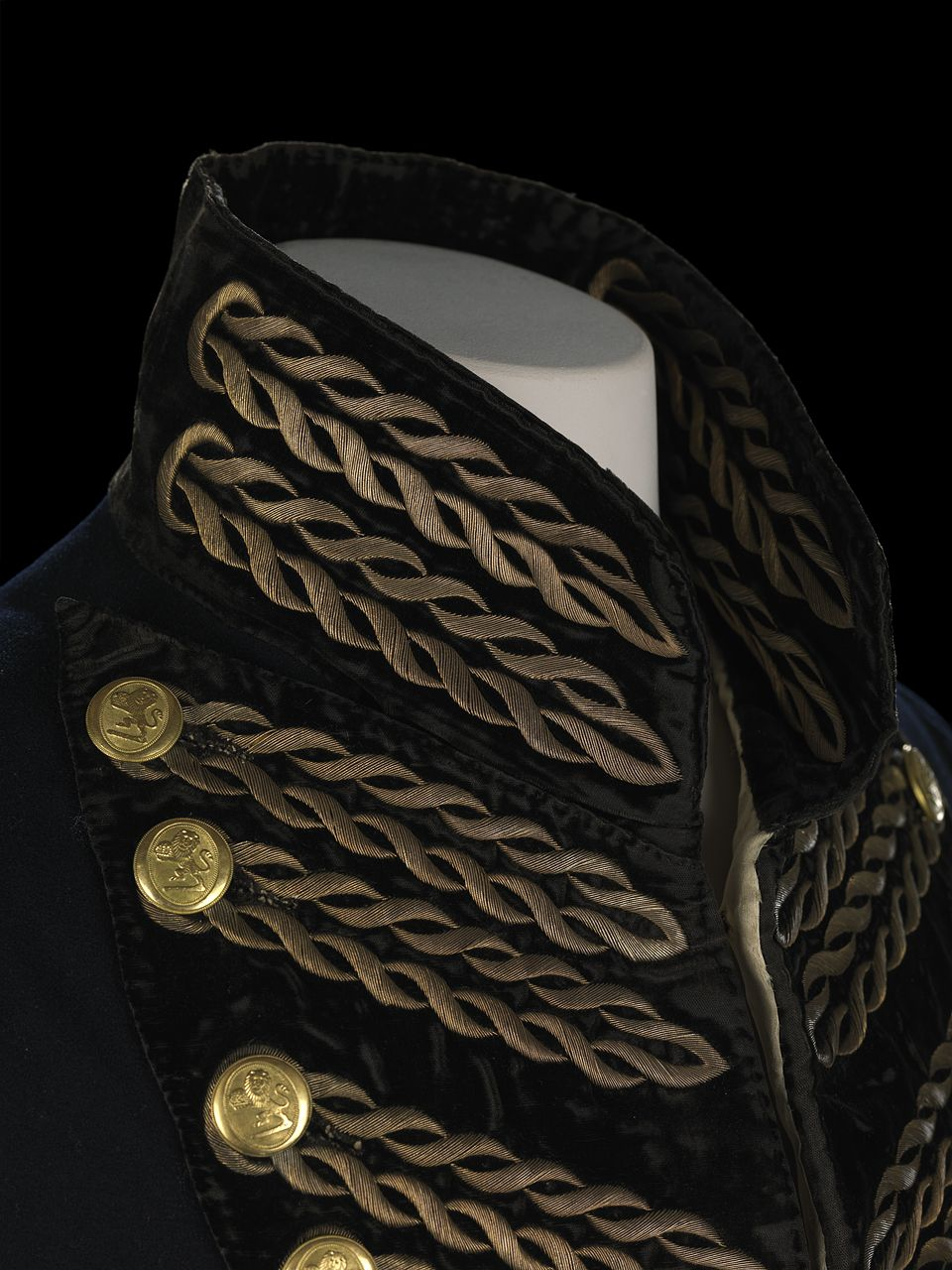 The coat has a two exterior pocket flaps, with three points. Each pocket has four buttons with faux buttonholes outlined with metal thread embroidery. The exterior pockets are actually dummy pockets, the actual pocket is in the tails and is lined with linen. The sleeves are also lined with white silk twill, and the cuffs are of black velvet with four buttons arranged in pairs, the button holes are outlined with metal thread embroidery.
