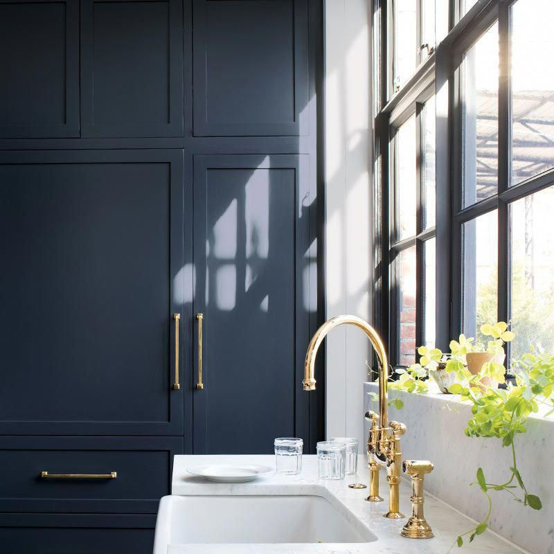Navy-painted cabinets in a sleek kitchen with marble ...