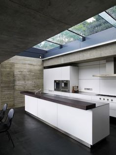 Love the off form concrete and the retractable skylight over the kitchen island.