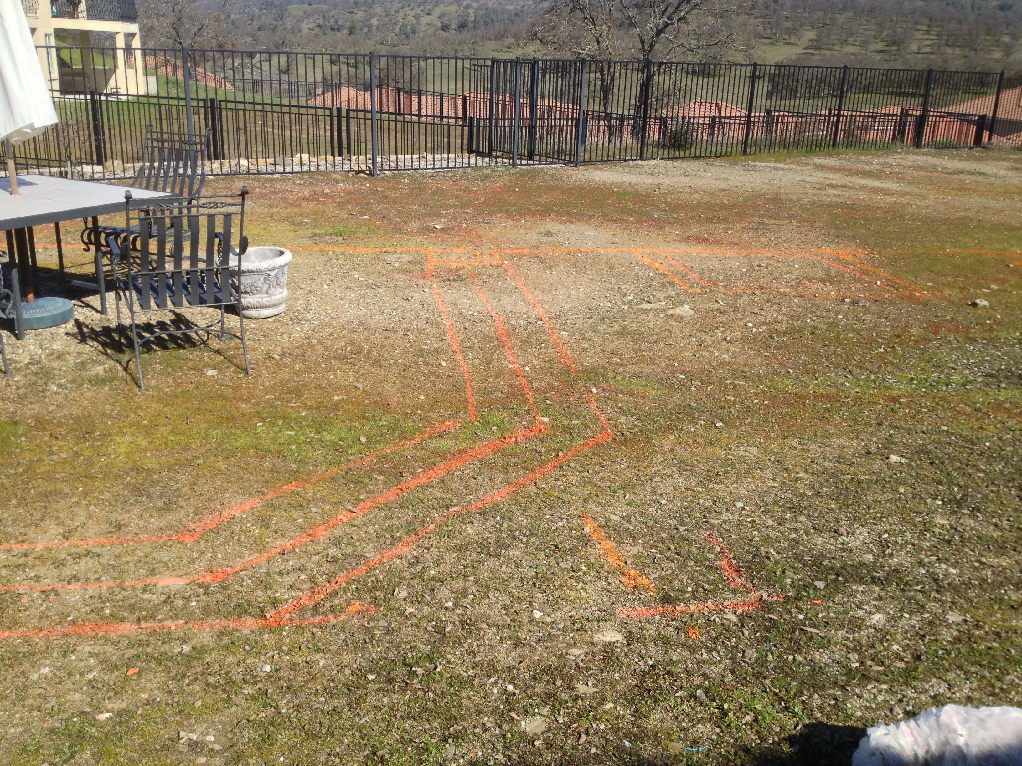layout of design of the raised deck with spray paint on dirt