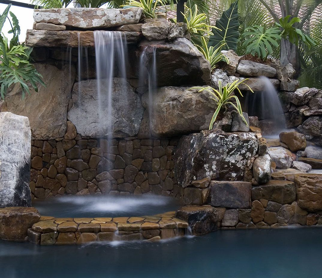 All Stone Grotto Waterfall Overhanging A Spa. LUCAS